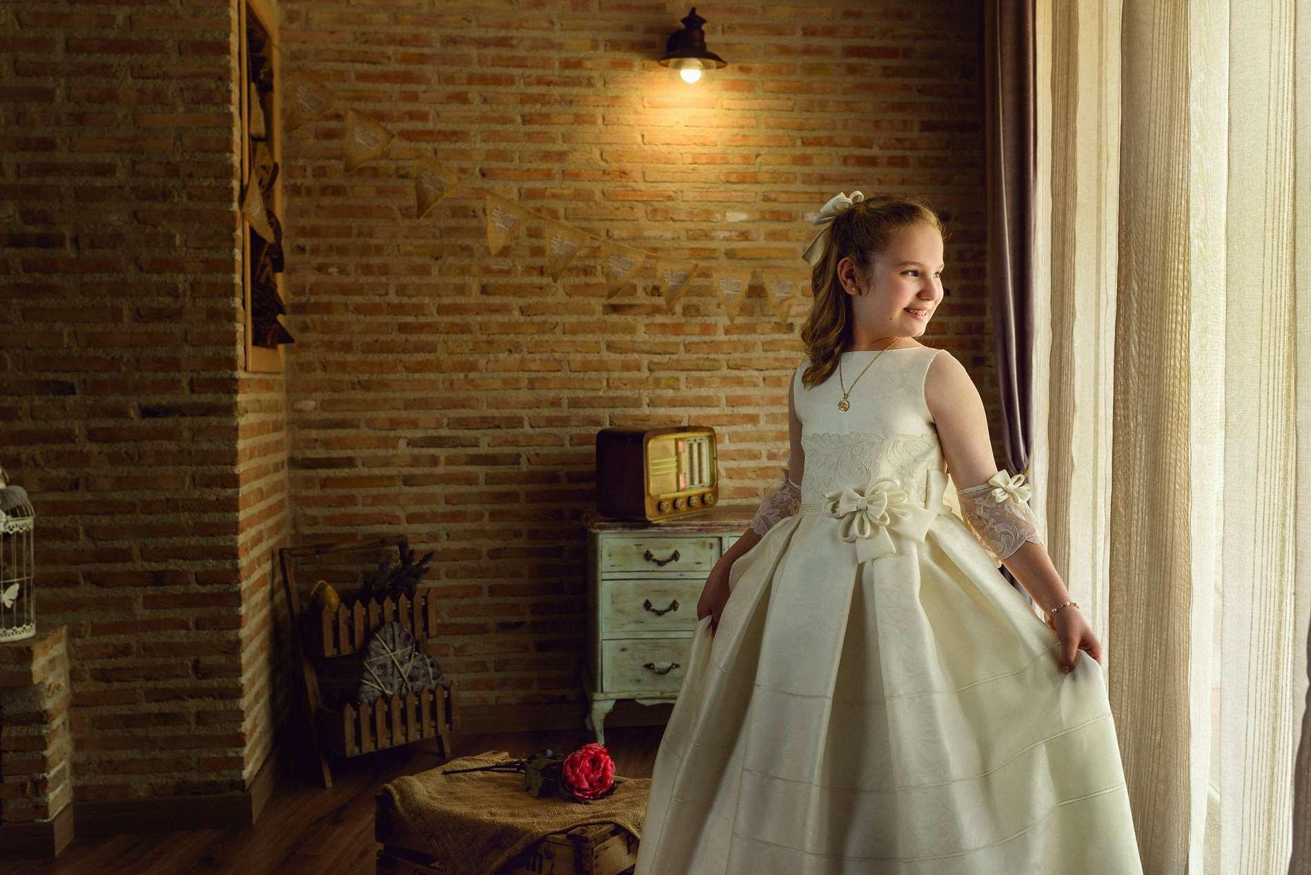 con su vestido en la ventana